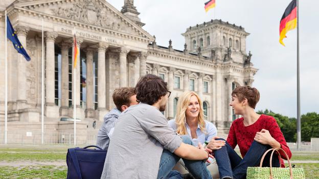 Vier Studierende sitzen vor dem Berliner Reichstag.