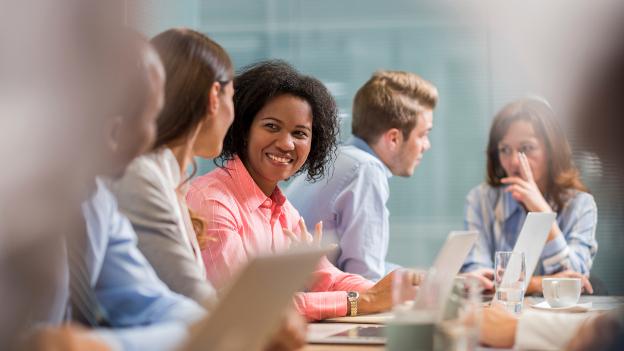 Internationale Alumni unterhalten sich sitzend an einem Tisch.