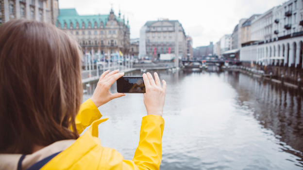 Eine Studierende fotografiert das Hamburger Rathaus mit dem Smartphone.