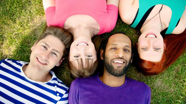 Internationale Studierende liegen lachend auf der Wiese.
