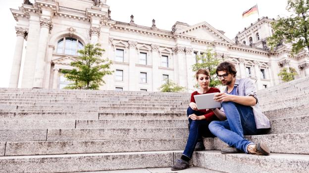 Studierende mit Tablet PC auf den Stufen des Berliner Reichstags.