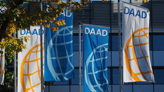 Fahnen mit dem DAAD-Logo vor der Außenfassade der Zentrale in Bonn.
