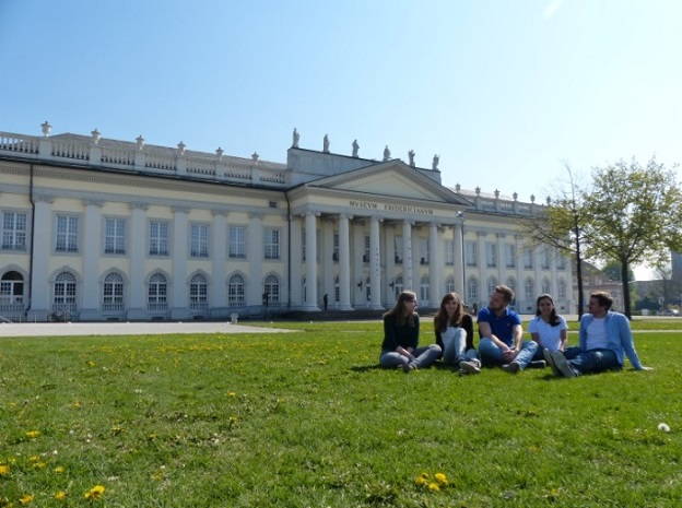 Students sitting on the grass in front of the Fridericianum in Kassel.